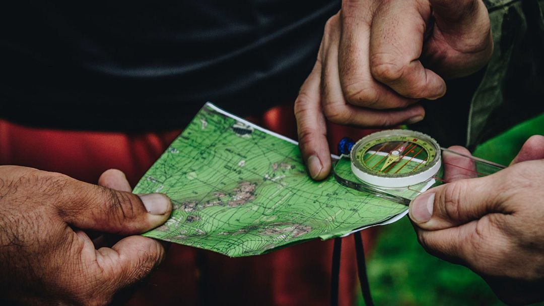 Close up of hands holding a map and compass